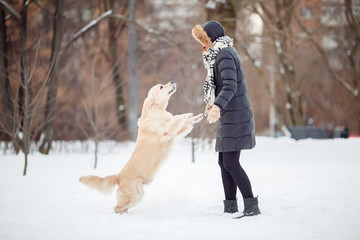 Picture of girl in black jacket playing with labrador at snowy park