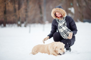 Picture of woman squatting next to labrador in winter park