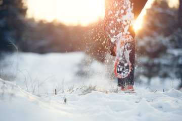 Photo of running man in sneakers on snowy forest in winter