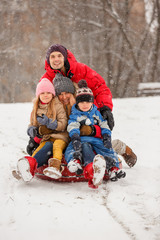 Photo of happy family with daughter and son sitting on tubing in winter