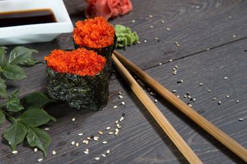 Tobiko-flying fish roe sushi. Japanese rice roll with seaweed at sushi bar