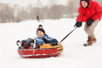 Photo of cheerful father skating son on tubing in winter afternoon