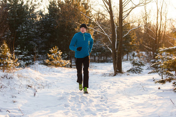 Picture of young athlete running through winter forest