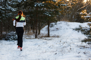 Picture from back of athlete in sneakers on morning run in winter forest