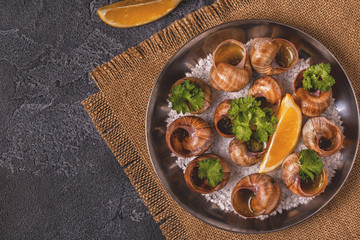 Fried snails with lemon, baguette and parsley.