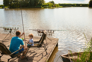 Father teaching son to fish at lakeside