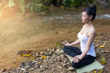 Young woman asia meditates while practicing yoga relax in nature