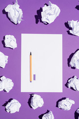 White blank page and a pen laying on a violet background