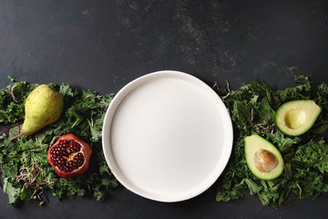 Green salad and fruits mix for salad or smoothie with kale, young beetroot leaves, sprouts, pear, avocado, pomegranate, white empty plate over dark texture surface. Top view, space. Food background.
