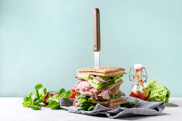 Beef and vegetables sandwiches with sliced meat, cucumber, green salad, rye whole grain bread in stack with knife on textil napkin over grey green pin-up style background. Ingredients above