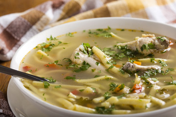 Chicken noodle soup with spoon and herbs