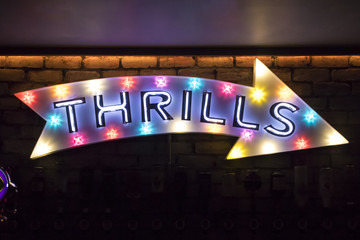 Illuminated wall mounted arrow sign with the word Thrils written on it