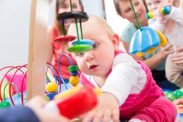 Baby erkundet die Welt in Kita oder Krabbelgruppe