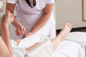 Female Enjoying Relaxing legs Massage In Cosmetology Spa Center