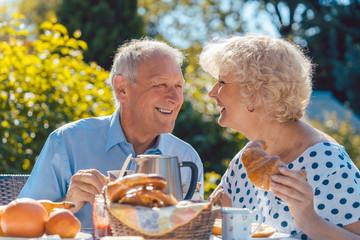 Glückliches Senioren Paar isst gutes Frühstück im Sommer Graten