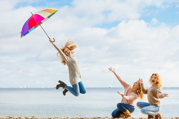 Women jumping with umbrella