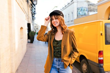 Summer sunny lifestyle fashion portrait of stylish woman walking on the street, wearing trendy outfit, holding her cap, smiling enjoy her weekends, smiles