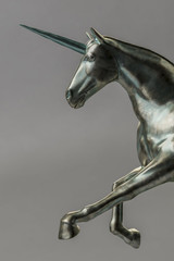 a beautyful bronze unicorn figure isolated on gray background