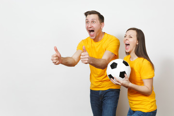 Fun crazy cheerful emotional young couple, woman, man, football fans in yellow uniform cheer up support team with soccer ball isolated on white background. Sport, family leisure, lifestyle concept.