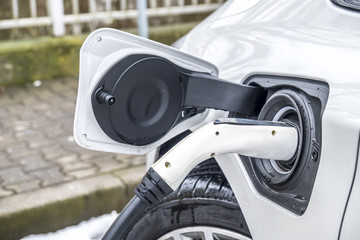 View of an Electric Car Charging and in the background a partial view of a car