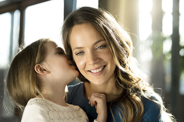 Smiling girl whispering into her mother's ear