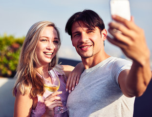 Positive loving young couple making selfies