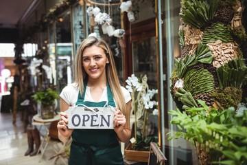 Female florist holding open signboard