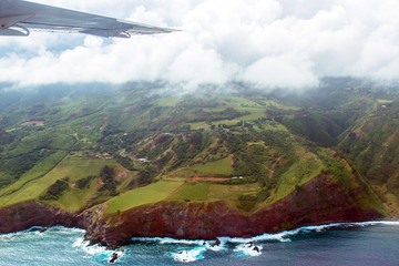 Aerial view of Maui's coastline shows everything from Pacific surf to rocky cliffs to green meadows to mountains to clouds and the wing of a small airplane