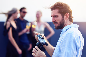 Handsome bearded man holding a photo camera