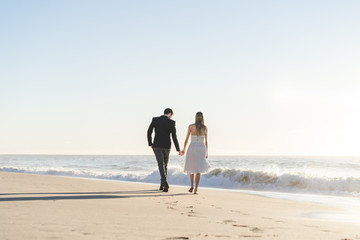 Romantic bride and groom strolling on beach