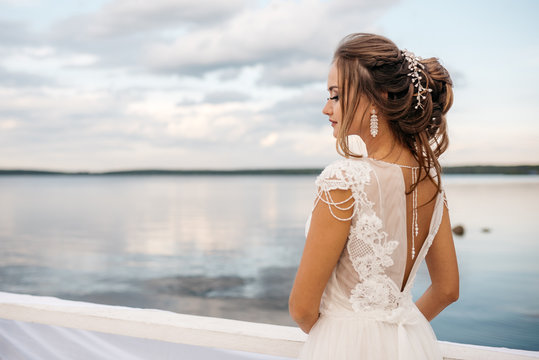A beautiful bride is standing on the pier. Water surface and cloudy sky on the background