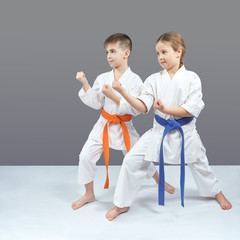 A girl and a boy in karategi stand in a karate rack