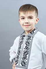 In a beautiful shirt the boy poses on a gray background