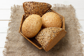 Bread rolls in the basket on rustic wooden background
