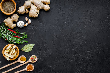 Condiments, seasoning and spices concept. Dry spices in wooden spoons near ginger, rosemary, chili pepper on black background top view copy space