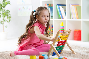 smiling kid girl playing with counter toy in nursery room