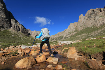 Young woman with backpack walking through the small river on high altitude mountain