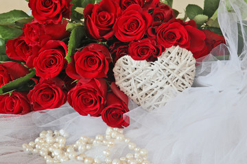 Scene with white wicker heart, pearl necklace on a veil and bunch of beautiful bright red roses on a background. Love and wedding concept.