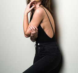 Sexy Woman Against a White Wall in a Black Tank Top and Black Jeans