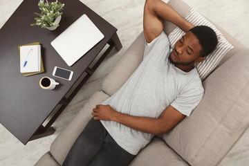 Handsome young african-american man relaxing on the couch at home