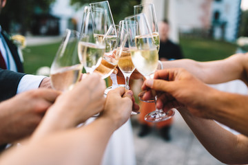 People hold in hands glasses with champagne, friends celebrating and toasting