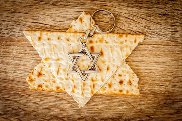 "Two pieces of matzah make up a Jewish Star of David (""Magen David"") with a Jewish key chain metal hexagram star. Pessach stock image, Jewish Passover holiday."