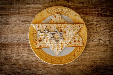 "Two pieces of matzah make up a Jewish Star of David (""Magen David"") with a Jewish key chain metal hexagram star on a plate, vintage background. Pessach stock image, Jewish Passover holiday."