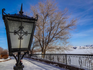 street lamp and winter view of the embankment with a fence against the blue sky
