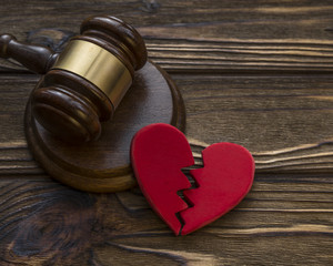 figure of a broken red heart, gavel, hammer of a judge on a wooden background. Divorce proceedings, the dissolution of marriage. court, law.