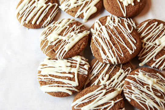 Brown Round Christmas Gingerbread cookies drizzled with White Chocolate on a plate.
