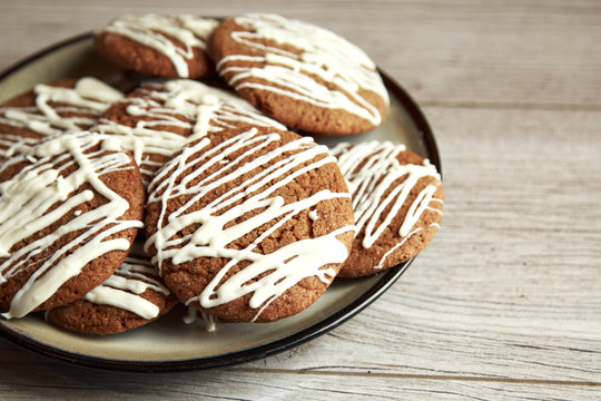 Brown Round Christmas Gingerbread cookies drizzled with White Chocolate on a plate