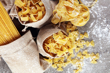 Various mix of pasta on grey rustic background. Diet and food concept.