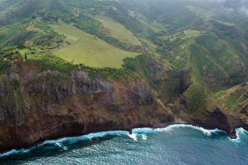 Aerial view of green meadows and rocky cliffs on the coast of the island of Maui in Hawaii, shot from a small, low-flying prop plane