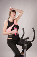 Woman on an exercise bike holding a plastic water bottle